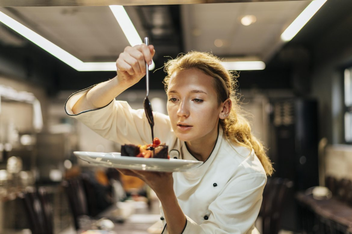 female-chef-carefully-pouring-sauce-dish